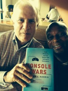 "Tom Kalinske and former NFL superstar Ronnie Lott take a photo holding the ""Console Wars"" book."