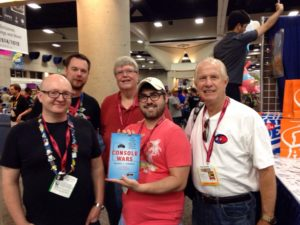 """Console Wars"" author Blake Harris (center) takes a photo with Tom Kalinske (right) and Al Nilsen (back, center) during the New York Toy Fair."